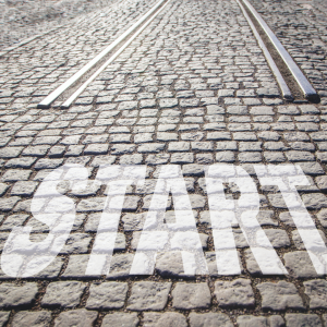 A cobbled road and tram track with the word Start at the bottom